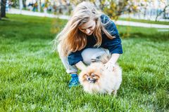Young teen girl playing with her dog Pomeranian Spitz on the grass in the city park royalty free stock image