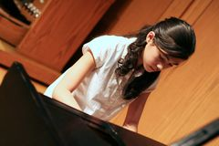 Young teen girl playing piano. Young teenage girl playing music on the grand piano at a recital Royalty Free Stock Photos