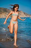 Young teen girl playing with waves at the beach. Stock Photos