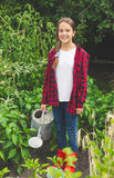 Young teen girl posing with watering can at garden Stock Photos