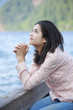 Young teen girl praying quietly on lake pier Stock Photos