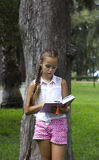 Young teen girl reading book near the pine tree. Young teen girl reading book near pine tree stock photography