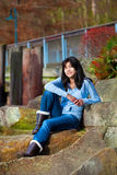 Young teen girl relaxing on large boulder along lake shore, smiling Royalty Free Stock Photos