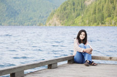 Young teen girl relaxing quietly on lake pier, Stock Photo