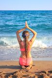 Young teen girl sitting on the beach looking to the sea royalty free stock image