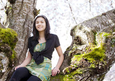Young teen girl sitting on branches of flowering cherry tree Royalty Free Stock Photos