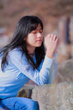 Young teen girl sitting outdoors on rocks praying Stock Image