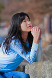 Young teen girl sitting outdoors on rocks praying Royalty Free Stock Images