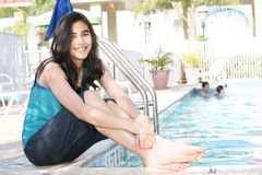 Young teen girl sitting by pool Royalty Free Stock Image