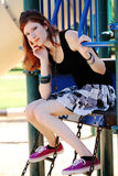 Young teen girl in skirt on playground equipment Royalty Free Stock Photography