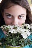 Beautiful Young Teen Girl Smelling Verbena Flowers. Young teen girl smelling a pot of white Verbena flowers Stock Image