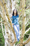 Young teen girl standing on branches in birch tree, smiling Royalty Free Stock Images