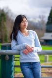 Young teen girl standing, leaning against railing at park Stock Images