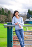 Young teen girl standing, leaning against railing at park Stock Photos