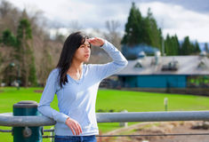 Young teen girl standing, leaning against railing at park shading eyes to look off to side Royalty Free Stock Photo