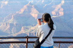 Young teen girl standing at railing taking pictures at Grand Can Stock Image