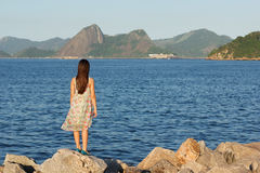 Young teen girl standing on stones in dress with long brown hair Royalty Free Stock Photo