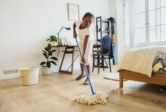 Young teen girl sweeping up the floor Stock Photos
