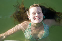 Young teen girl swimming in water Stock Images