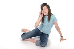 Young Teen Girl Talking On Cellphone 1. Cute tween or young teenage girl sitting on the floor and talking on a cellphone; shot on white Stock Image