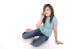 Young Teen Girl Talking On Cellphone 2. Cute tween or young teenage girl sitting on the floor and talking on a cellphone; shot on white Stock Photography