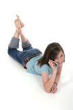 Young Teen Girl Talking On Cellphone 6. Cute tween young teenage girl sitting on the floor and talking on a cellphone; shot on white Royalty Free Stock Photo