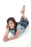 Young Teen Girl Talking On Cellphone 7. Cute tween or young teenage girl sitting on the floor and talking on a cellphone; shot on white royalty free stock photography