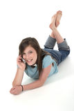 Young Teen Girl Talking On Cellphone 8. Cute tween or young teenage girl sitting on the floor and talking on a cellphone; shot on white Royalty Free Stock Photo