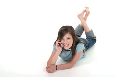 Young Teen Girl Talking On Cellphone 9. Cute tween or young teenage girl sitting on the floor and talking on a cellphone; shot on white Royalty Free Stock Image
