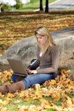 Young teen girl using laptop - autumn. Beautiful young teen girl sitting in park using laptop (autumn Stock Photos