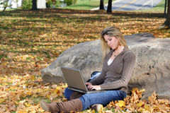 Young teen girl using laptop - autumn. Beautiful young teen girl sitting in park using laptop (autumn royalty free stock photo
