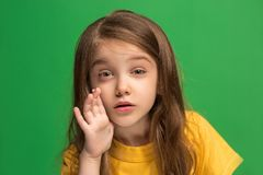 The young teen girl whispering a secret behind her hand over green background. Secret, gossip concept. Young teen girl whispering a secret behind her hand royalty free stock photo