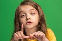 The young teen girl whispering a secret behind her hand over green background. Secret, gossip concept. Young teen girl whispering a secret behind her hand stock photography
