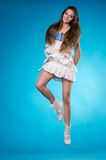 Young teen girl in a white lace dress jumping Stock Image