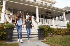 Young teen girlfriends leaving a house for school stock photos