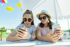 Young teen girls with mobile phones. Sit in a street cafe, sunny summer day in recreation and entertainment area. Young teen girls with mobile phones. Sit in a royalty free stock photos