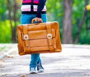 Young teen girt with suitcase in a park Royalty Free Stock Photo