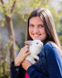 Young teen holding a baby white dwarf rabbit royalty free stock photo