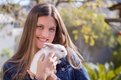 Young teen holding a baby white dwarf rabbit stock photo