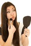 Young teen model applying blush with a brush fun expression Stock Images