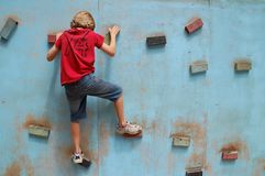 Climbing Wall Exercise. A young teen or pre-teen using a basic climbing wall royalty free stock photos