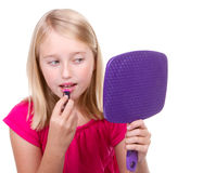 Young teen putting on lipstick Royalty Free Stock Images
