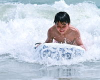 Young teen rides the waves defiantly. A 13 years old multi ethnic teen challenges the waves with defiance on a surf board Stock Image
