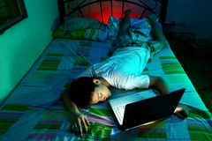Young Teen sleeping front of a laptop computer and on a bed. Photo of a Young Teen sleeping in front of a laptop computer and on a bed Stock Photography