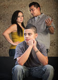 Young Teen Spacing Out. Young Latino boy in blank stare with concerned parents behind him Royalty Free Stock Image