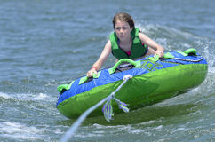 Young Teen Tubing Behind a Boat. A young girl hanging onto a tube behind a boat as it hits the waves Royalty Free Stock Image