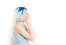 Young teen woman screaming on white. Young teen woman hipster style and blue hair profile screaming with hands on face, isolated on white Stock Images