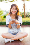 Young teen woman and smartphone in hand smiling with happy emoti Stock Images