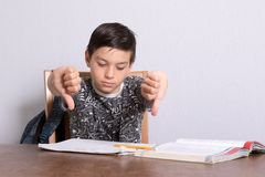 Young teenage boy doing his homework. While giving thumbs down gesture Stock Images