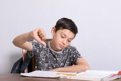 Young teenage boy doing his homework. While giving thumbs down gesture Stock Image
